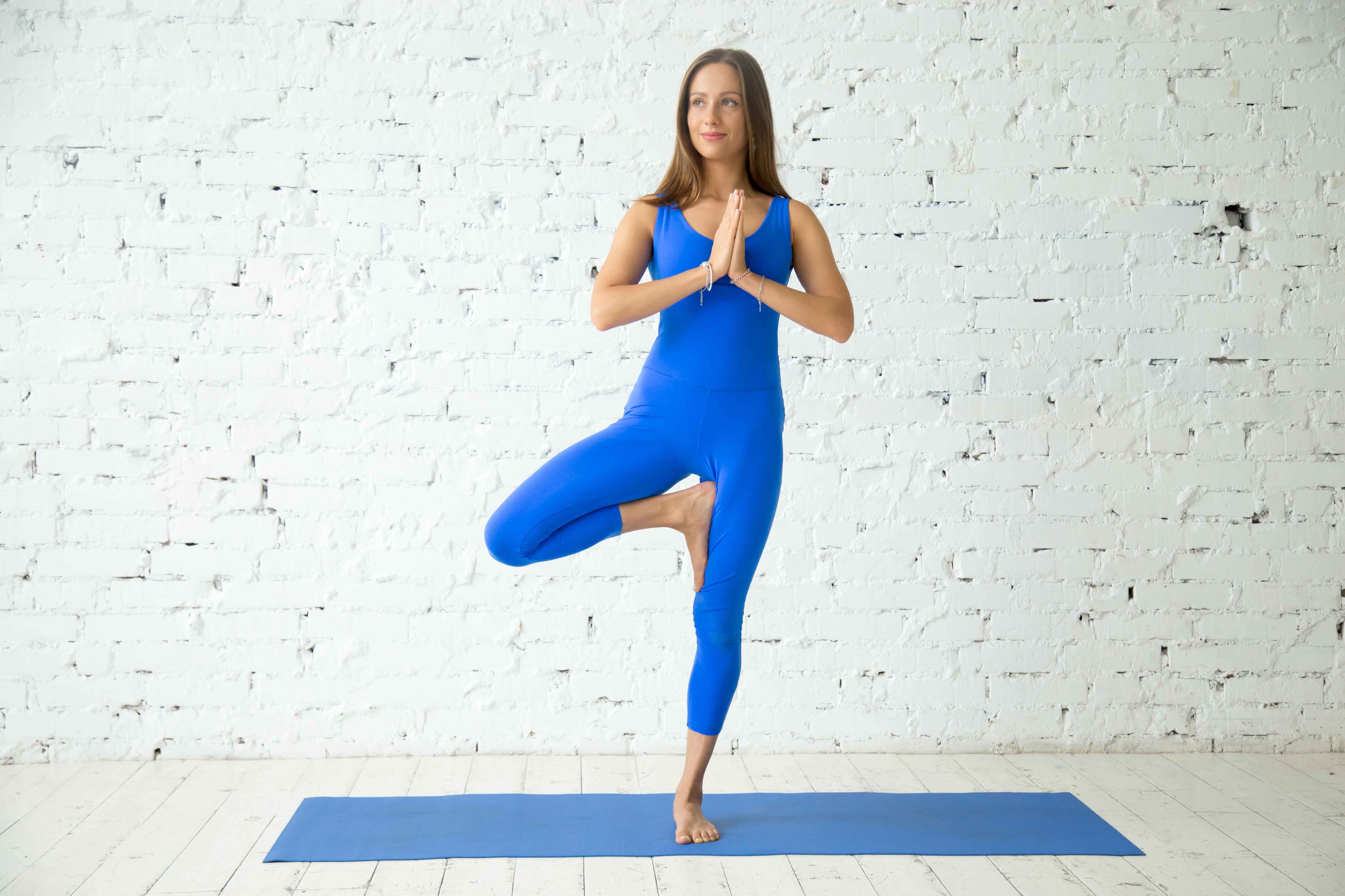 Young attractive woman in Tadasana pose, white studio background