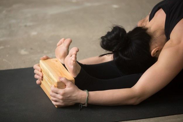 young-attractive-woman-in-paschimottanasana-pose-with-block-clo_1163-3065