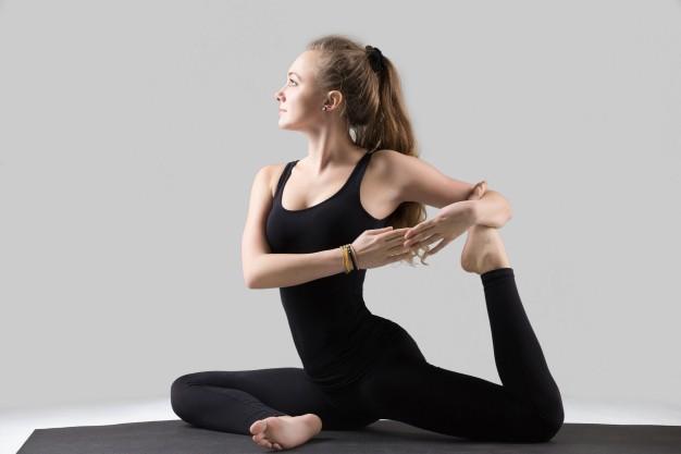 young-woman-in-one-legged-king-pigeon-pose-grey-studio_1163-2933