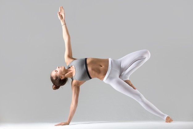 young-woman-in-side-plank-pose-grey-studio-background_1163-2484